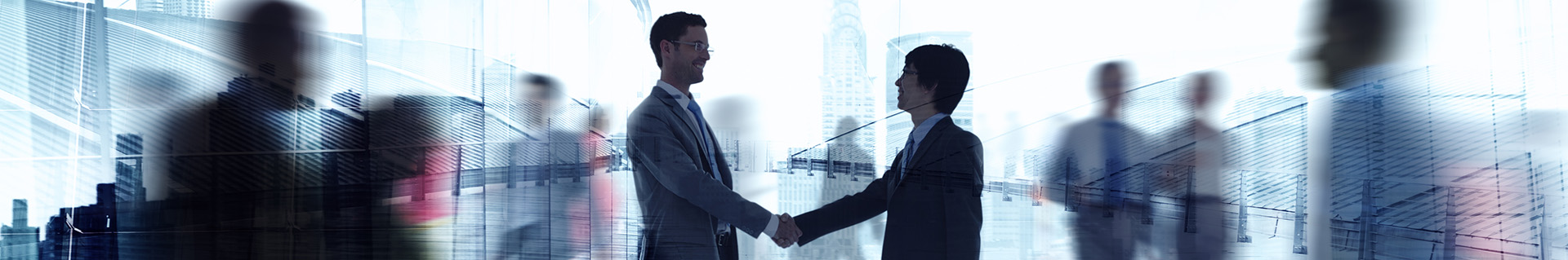 Two businessmen shaking hands in front of cityscape