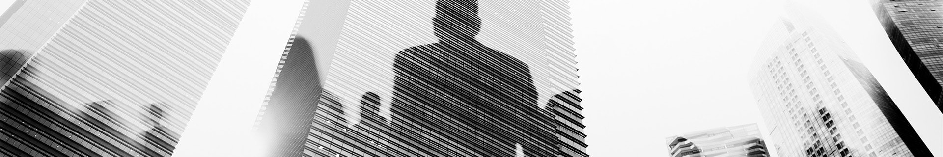 Corporate skyscrapers and offices, with human outlines reflecting off them