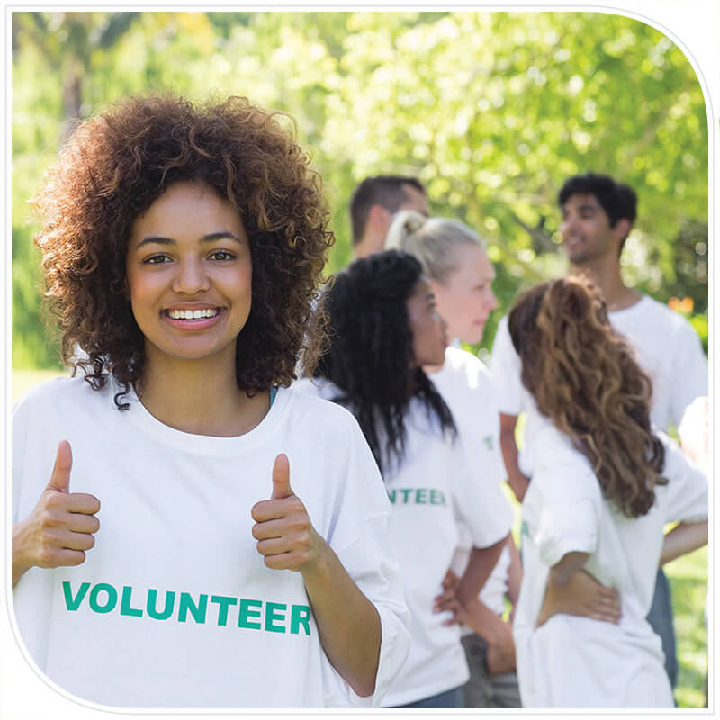Volunteer woman smiling with thumbs up infront of volunteer group