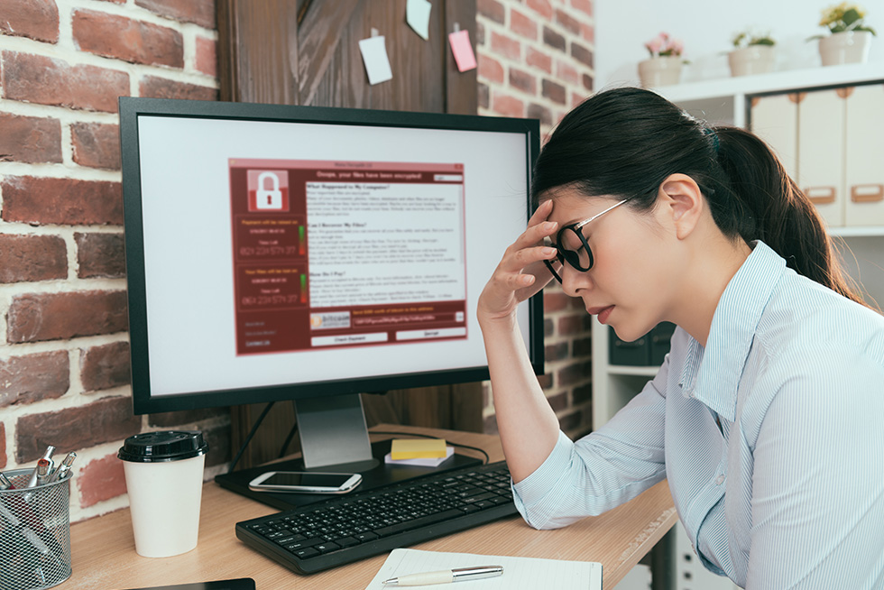 Woman hangs her head at ransomware on screen
