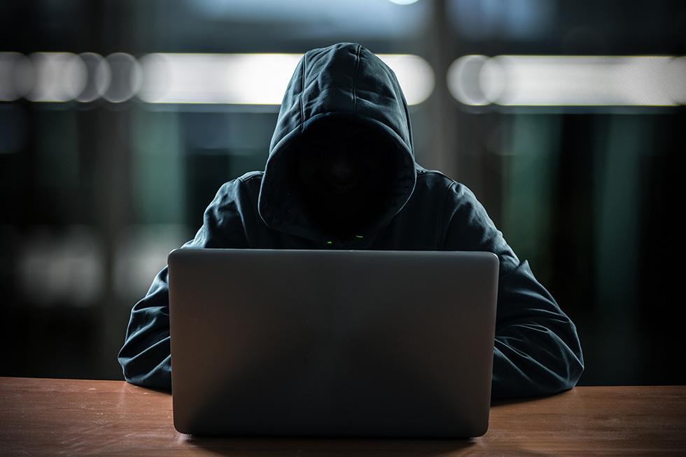 Hooded man working on laptop