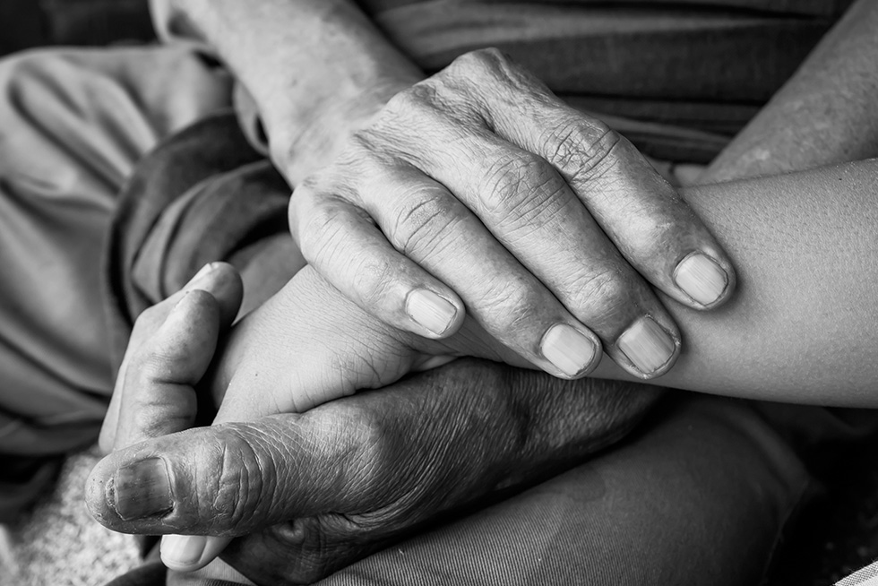 A woman holds the hand of an elderly man