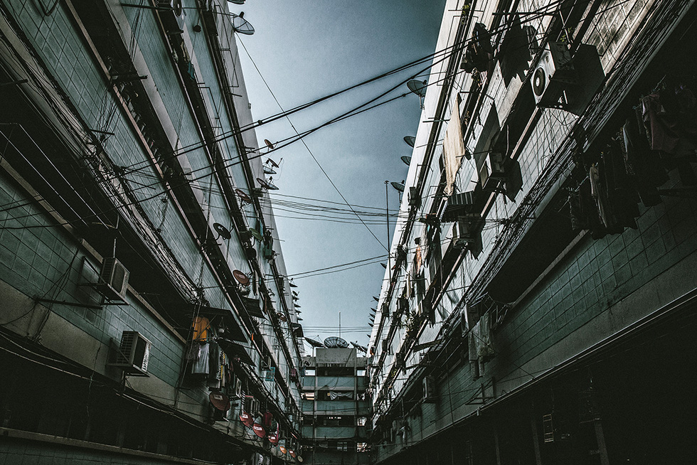 An alley between apartments with many wires criss-crossed above