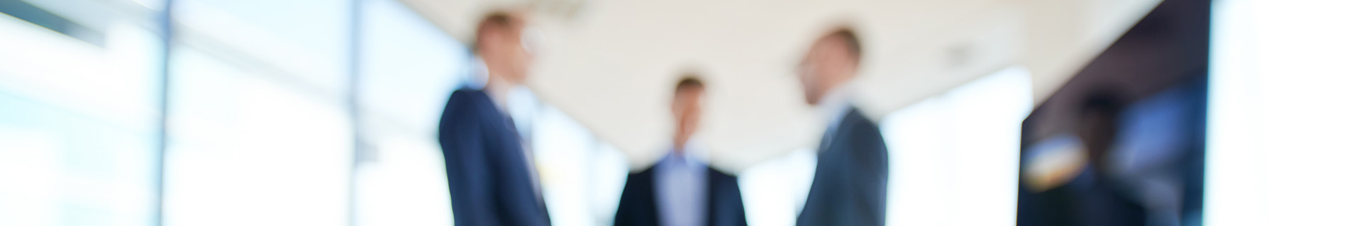 Blurred image of 3 businessmen discussing orders