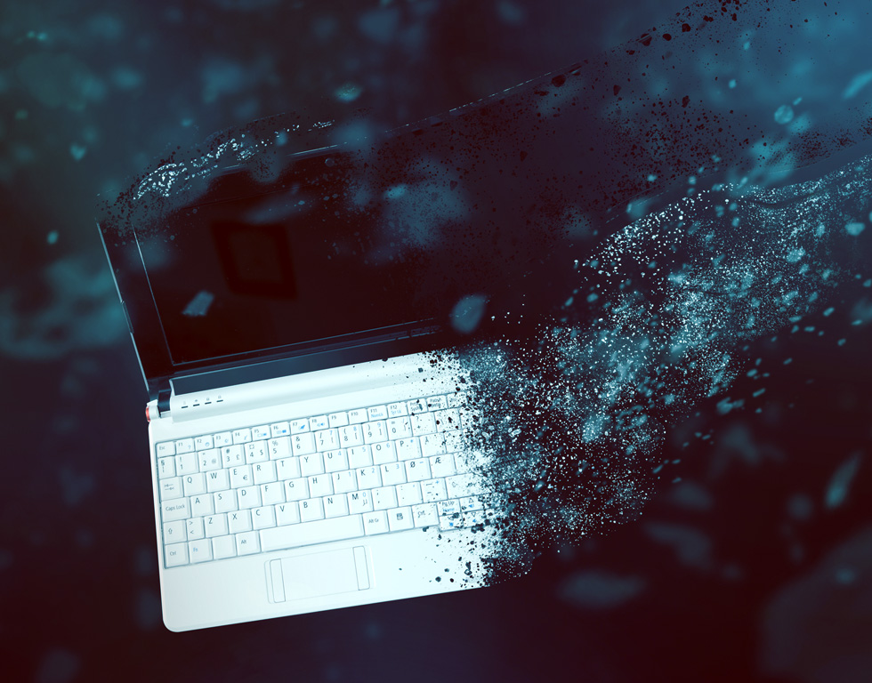 A laptop disintegrating into dust