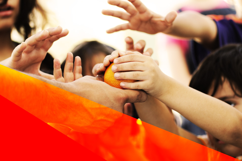 Children grasping at an orange