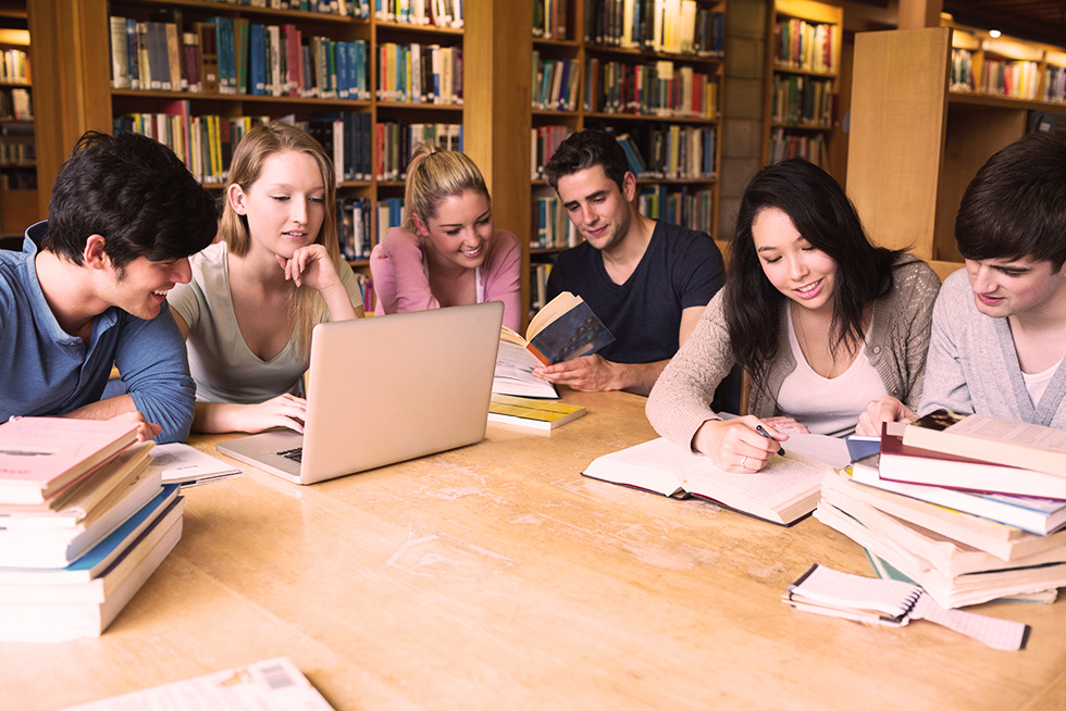Group of students working in a library