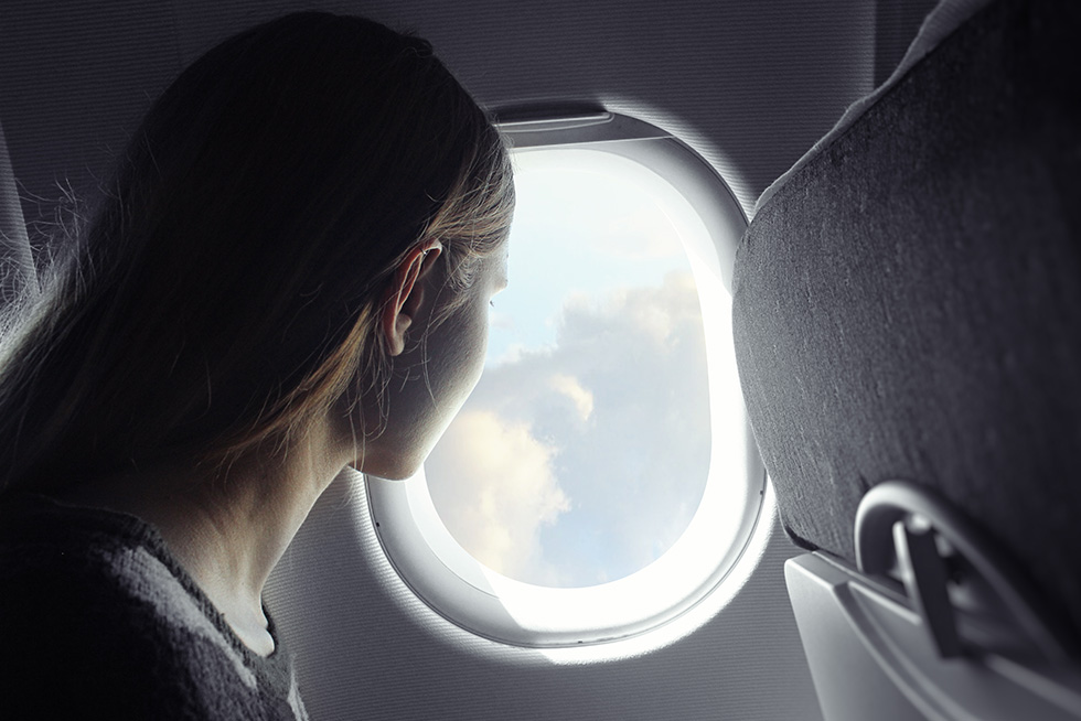 Woman looks out window of a plane