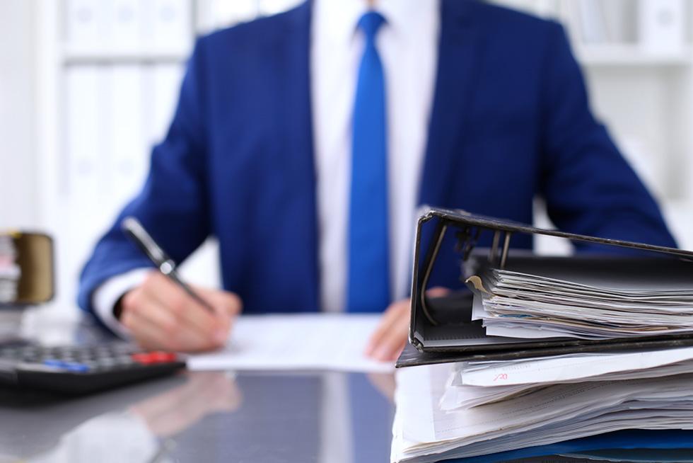 Businessman writing report at desk