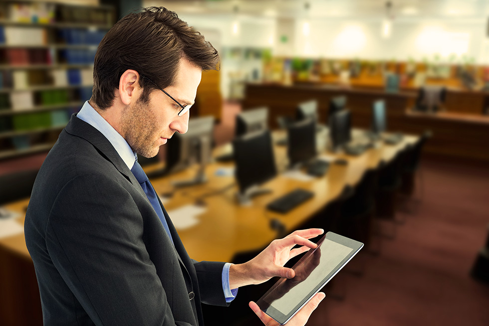 Man using his tablet while in a library