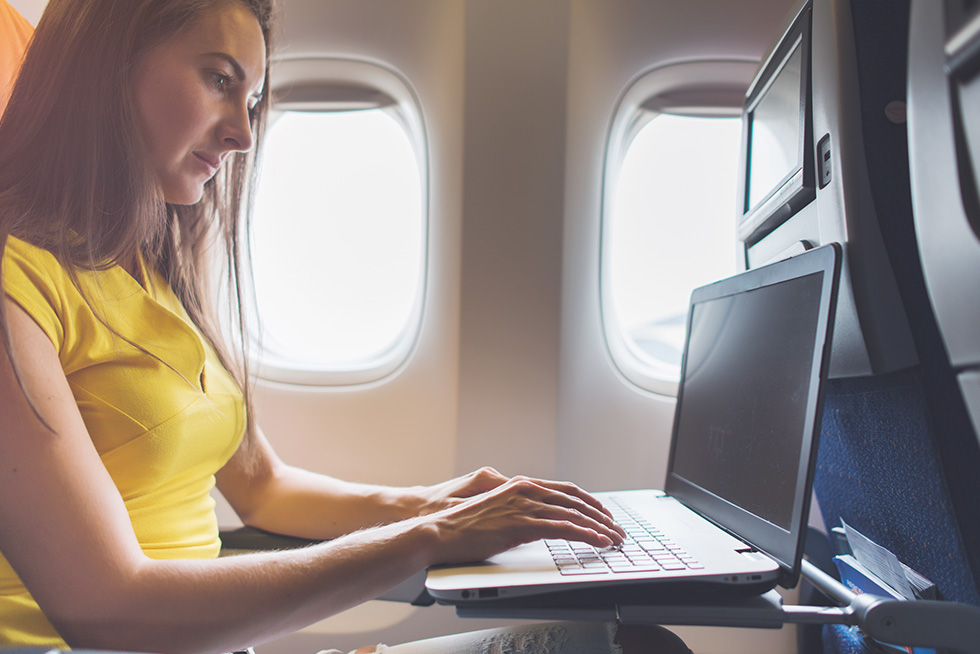 Woman working on a laptop on-board a plane