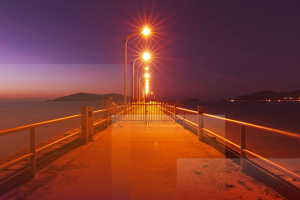 A look down a streetlamp lit pier at dusk